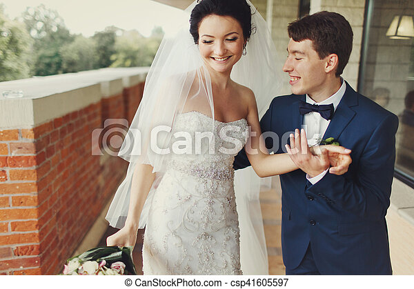Groom holds bride\'s hand leading her along the balcony
