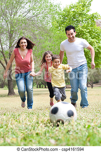 Parents and two young children playing soccer in the green field, outdoor - csp4161594