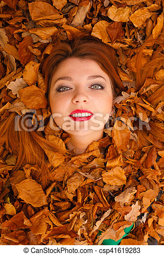 Art symbolism nature outdoor fun concept. Young ginger covered by leaves. Redhead girl drowning in foliage sticking her face out.