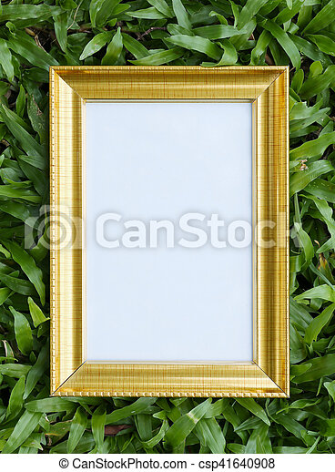 Gold picture frame on green lawn in top view for the design nature background.