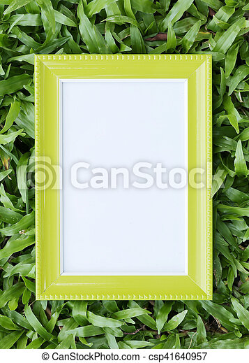 Yellow picture frame on green lawn in top view for the design nature background.