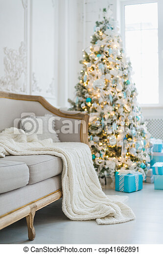 Calm image of interior luxury home living room decorated christmas tree and gifts, sofa covered with blanket. Selective focus.