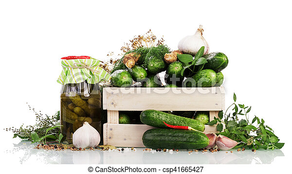 Fresh cucumbers in a wooden box and a jar of pickled spices isolated on a white background.