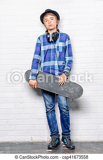 Modern teenage boy with skateboard. Studio shot. Youth culture.