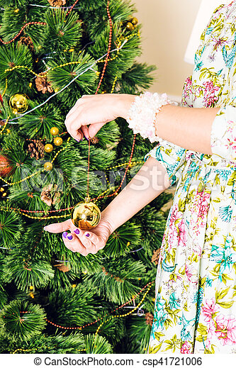 Christmas, decoration, holidays and people concept - close up of woman hand holding christmas gold ball.