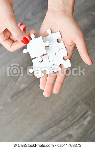 Woman hand fitting the right piece of puzzle suggesting business networking concept