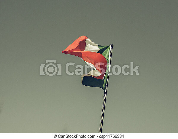 Vintage looking The national flag of Italy, Europe floating over blue sky