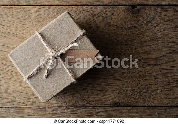 Overhead shot of a simple, rustic, plain brown gift box, tied with string and a blank tag for copy space Set on old Oak wood planking.
