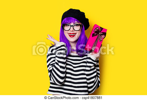 Portrait of a young woman in glasses with gift box on yellow background