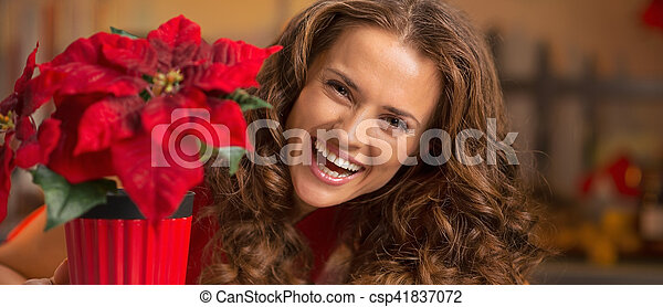 Smiling young woman looking out from christmas rose in christmas decorated kitchen