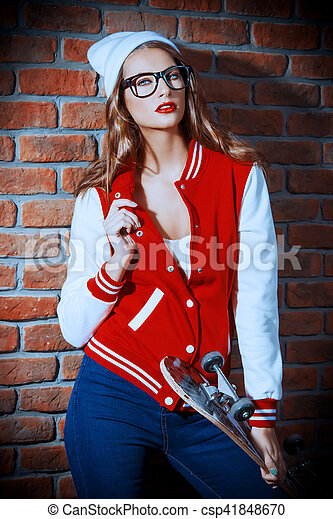Portrait of an attractive girl with bright red lips wearing modern sports clothes. College style. Hipster girl by a brick wall. Youth fashion.