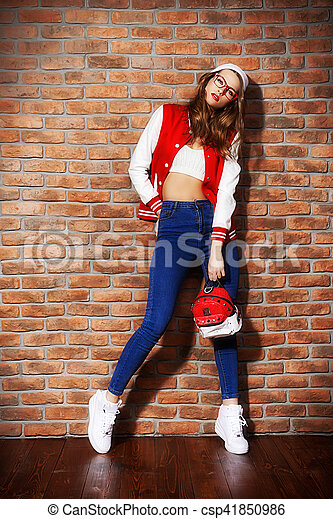 Fashion shot of a sexual girl with bright red lips wearing modern youth clothes. College style. Hipster girl by a brick wall. Youth fashion.