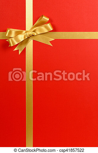Gold ribbon bow, red gift wrap background, copy space, vertical