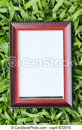 Brown picture frame on green lawn in top view for the design nature background.