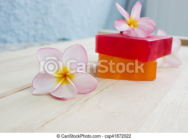 Soap and frangipani flower on wooden floor massage and spa concept background