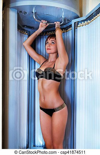 Slim woman in solarium getting sun tan - csp41874511
