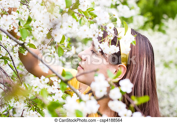 Young woman smelling spring cherry flowers - csp4188564