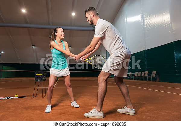 Learn together. Cheerful delighted young friends holding tennis racket and learning to play tennis in an indoor tennis court