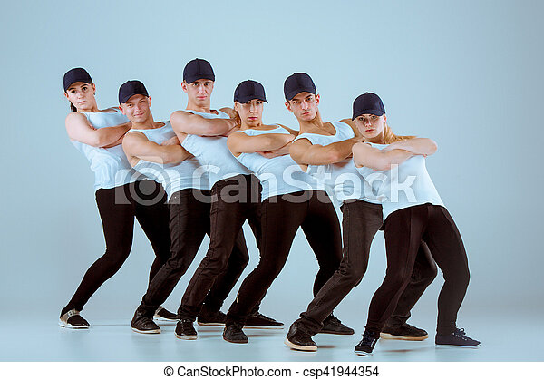 Group of men and women dancing fitness or hip hop choreography in gray studio background