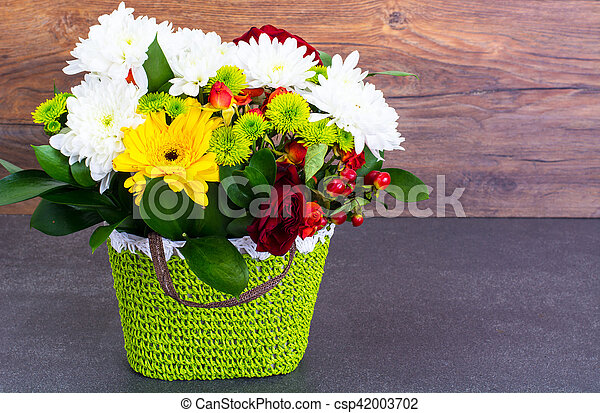 Floral arrangement of fresh flowers in the green wicker basket on old boards. Studio Photo