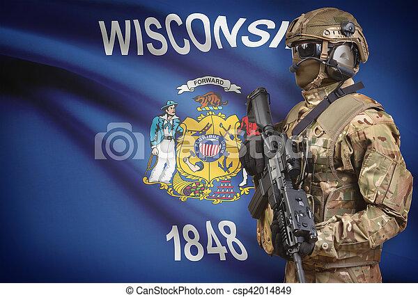 Soldier in helmet holding machine gun with USA state flag on background series - Wisconsin - csp42014849