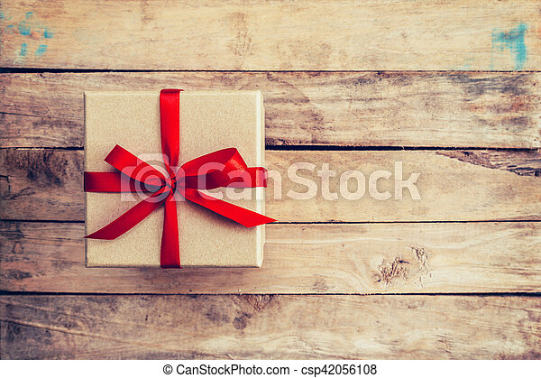 Brown gift box on wooden background. Vintage gift box on wooden background. Gift box with red ribbon on wood background with space.