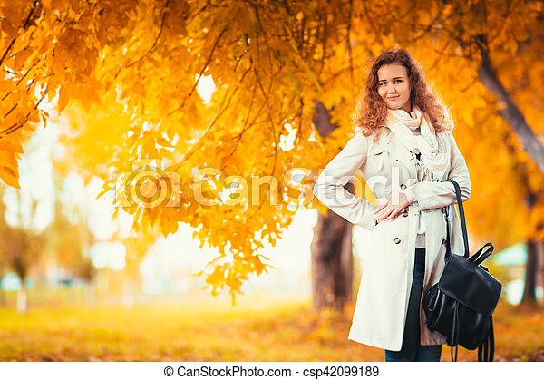 young girl in a light coat on the background of autumn park.