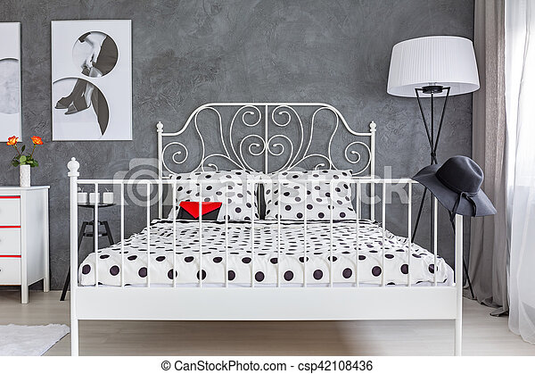 Grey bedroom with large bed with decorative metal headboard