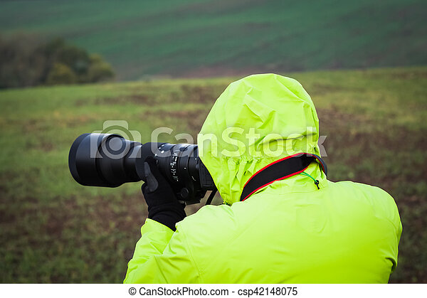 Photographer outdoors with big zoom lens as professional digital equipment getting ready to shoot a photo, wearing a bright jacket and gloves.