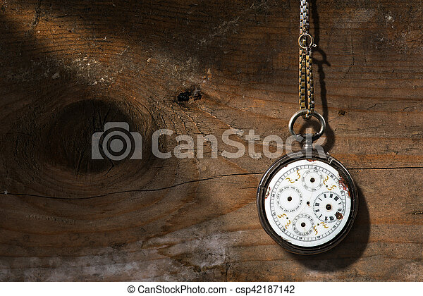 Old and vintage pocket watch with chain and without watch hands on a wooden background with copy space