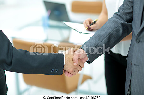 closeup of handshake of two businessmen in the background of the office
