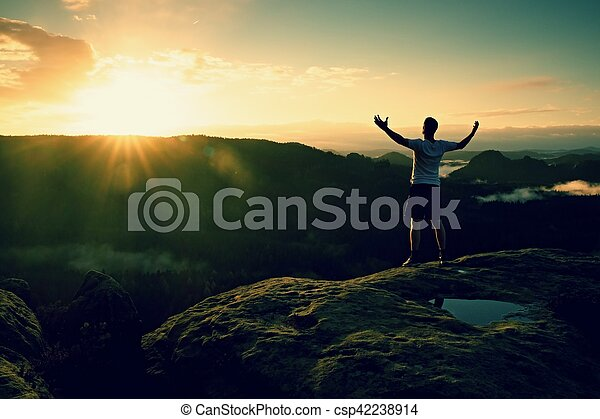 Runner on the peak. Man in his target gesture triumph with hands in the air. Crazy man in black pants and white t-shirt,