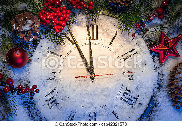 christmas clock with winter decoration on snow happy new year concept