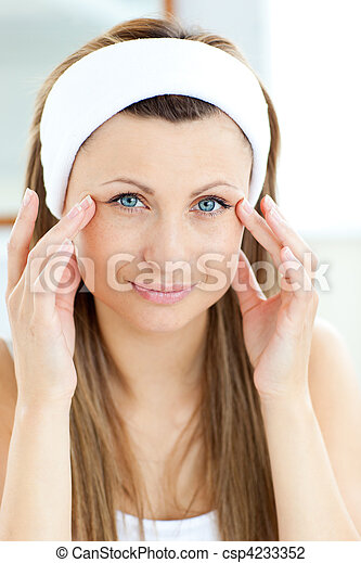 Portrait of a beautiful woman putting moisturizer on her face - csp4233352