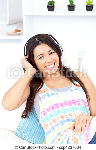 Radiant asian young woman listen to music with headphones on the couch smiling at the camera - csp4237684