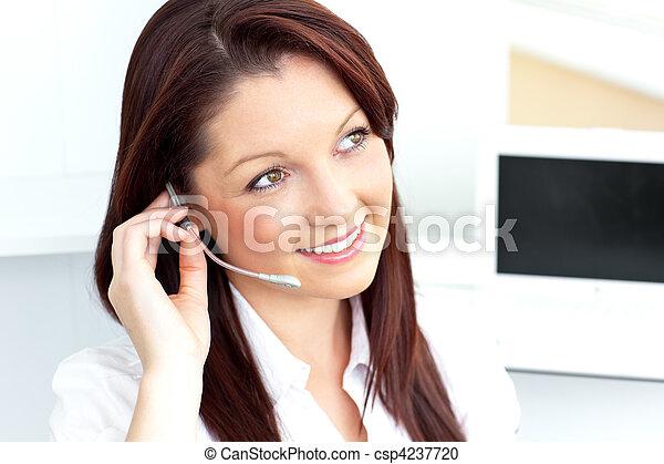 Pretty businesswoman talking on phone using headphones - csp4237720