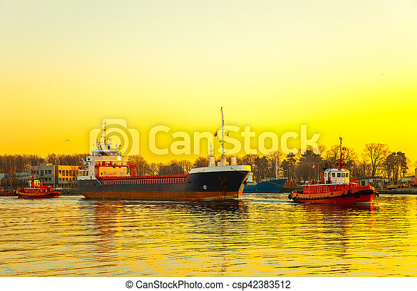 Tugboats assisting cargo ship in port at sunrsie.