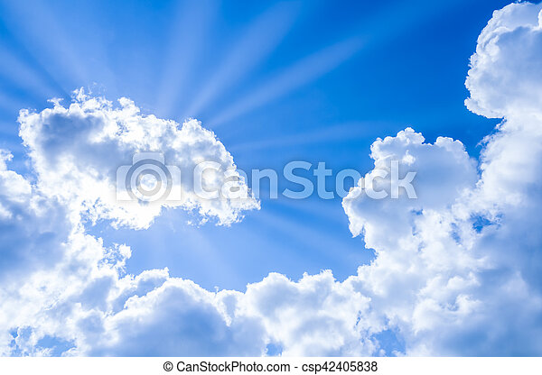 sun rays breaking through the clouds on blue sky - csp42405838