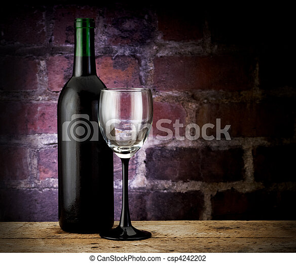 Wine bottle and glass on brick back - csp4242202
