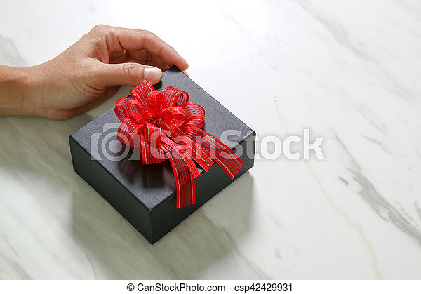 gift giving,man hand holding a gift box in a gesture of giving on white gray marble table background