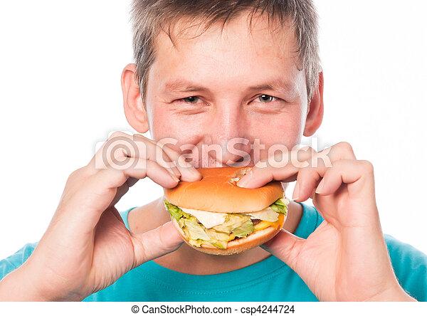 Hungry young man eating a hamburger - csp4244724