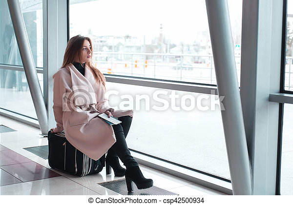 Passenger woman in airport waiting for air travel. Young business woman sitting with travel suitcase in waiting hall of departure lounge in airport