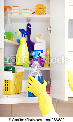 Woman with safety gloves storing cleaners in pantry on the wall
