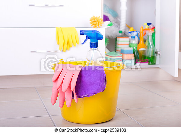 Spray bottle, cloth and rubber gloves in bucket on tiled floor in kitchen. Cleaning supplies and equipment stored in cabinet in background