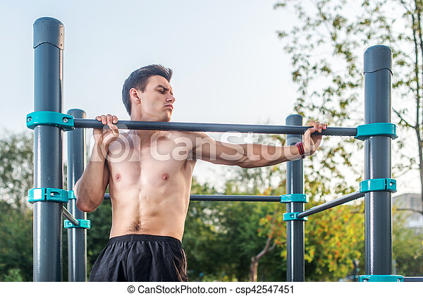 Young male athlete doing chin-up exercises in the park. Fitness man working out outside.