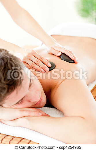 Resting man enjoying a massage with hot stone  - csp4254965
