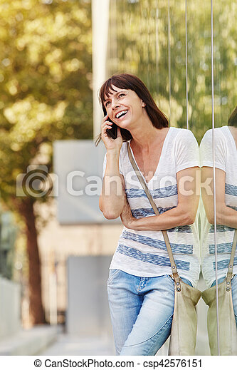Portrait of happy woman leaning on reflection talking on mobile phone