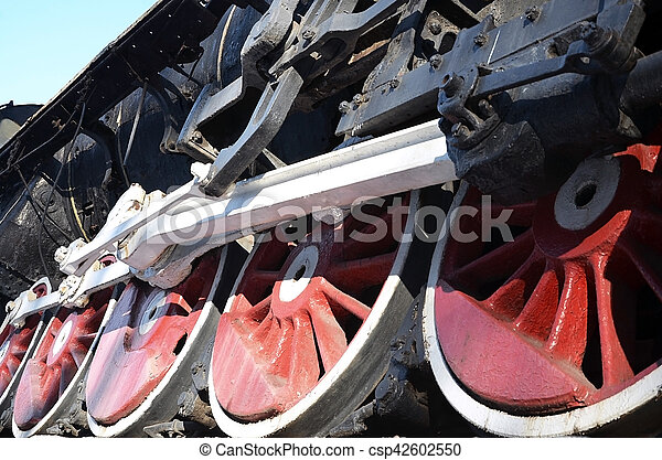Red wheels of old USSR black steam locomotive. Wheels of an old soviet steam train