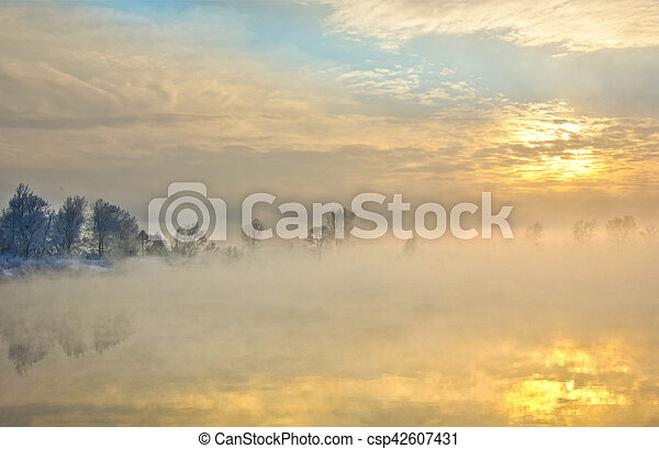Winter landscape. The sun shines in the photo camera. the trees and grass frost. water in the river heavy fog