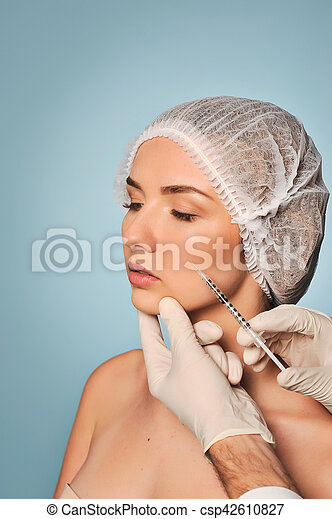 Beauty woman giving medical injections. The procedure carries a doctor in white medical gloves on a blue background